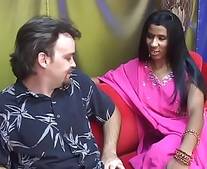 Youthful Indian lady gives an older man a blow job on a red couch